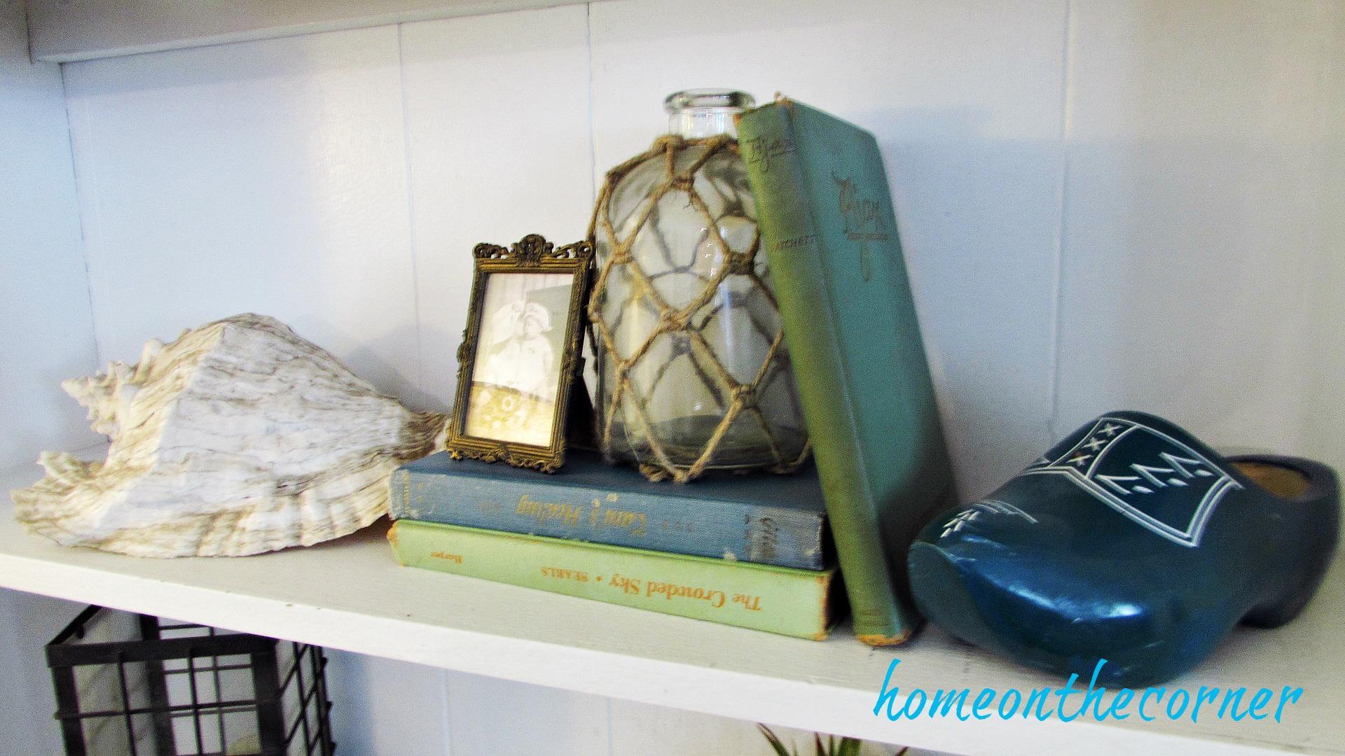 family room shelving seashell, wooden shoe, old books