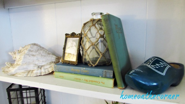 family room shelving seashell, wooden shoe, old books