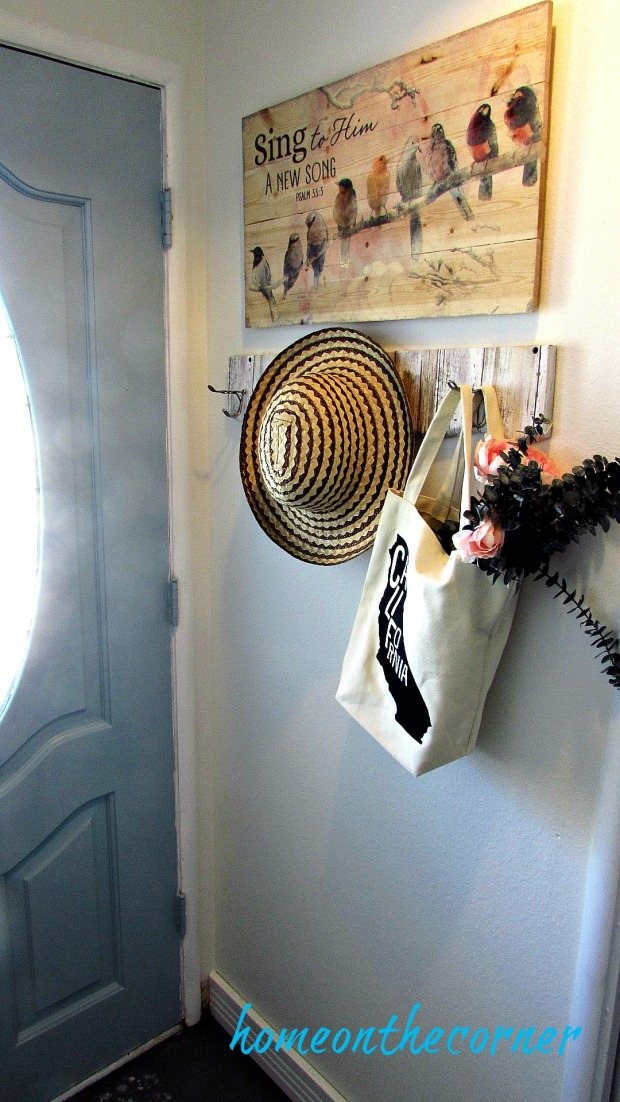 painted entryway wooden coat rack with hat and flowers