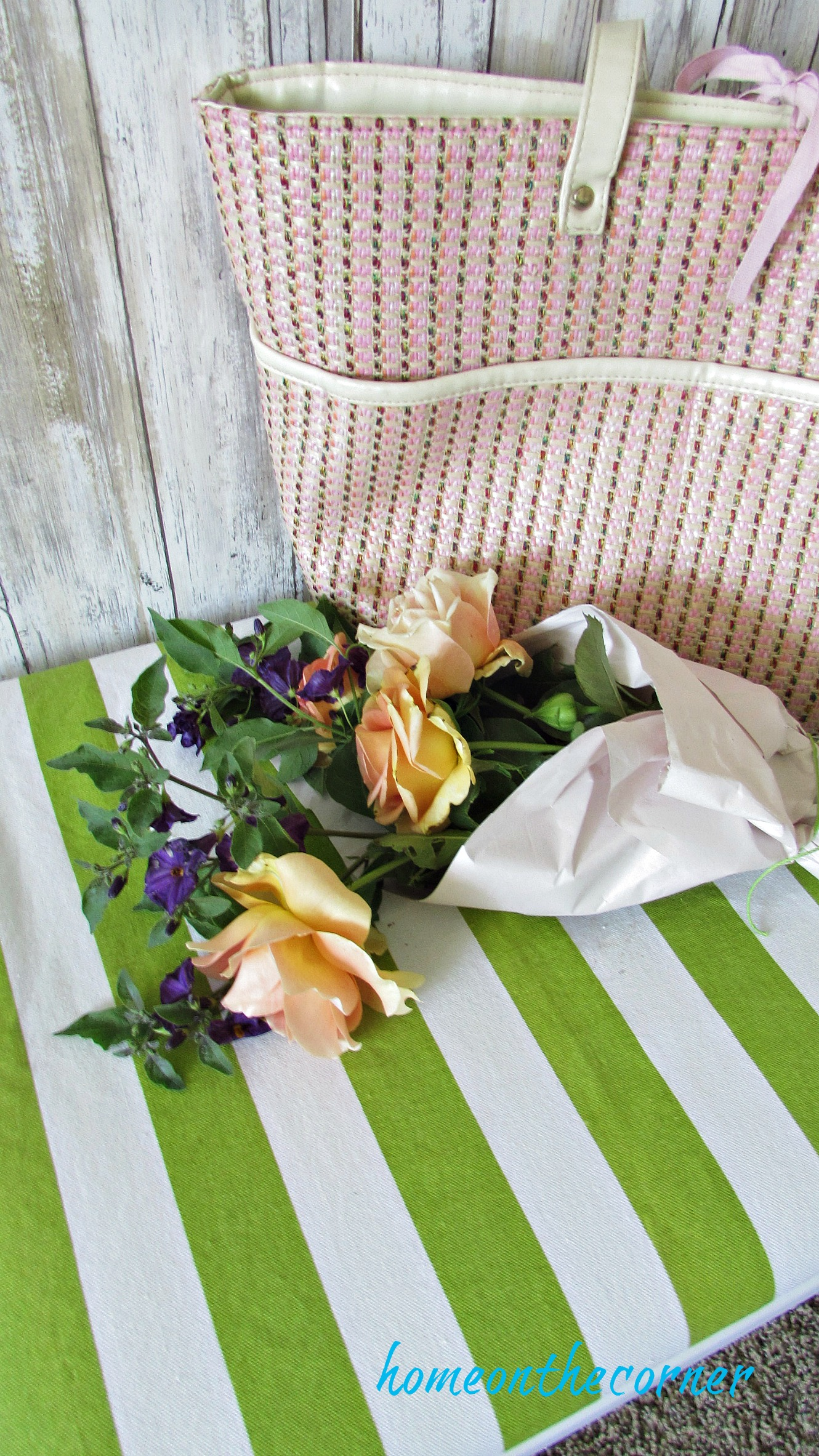 green and white striped bench with flowers and purse