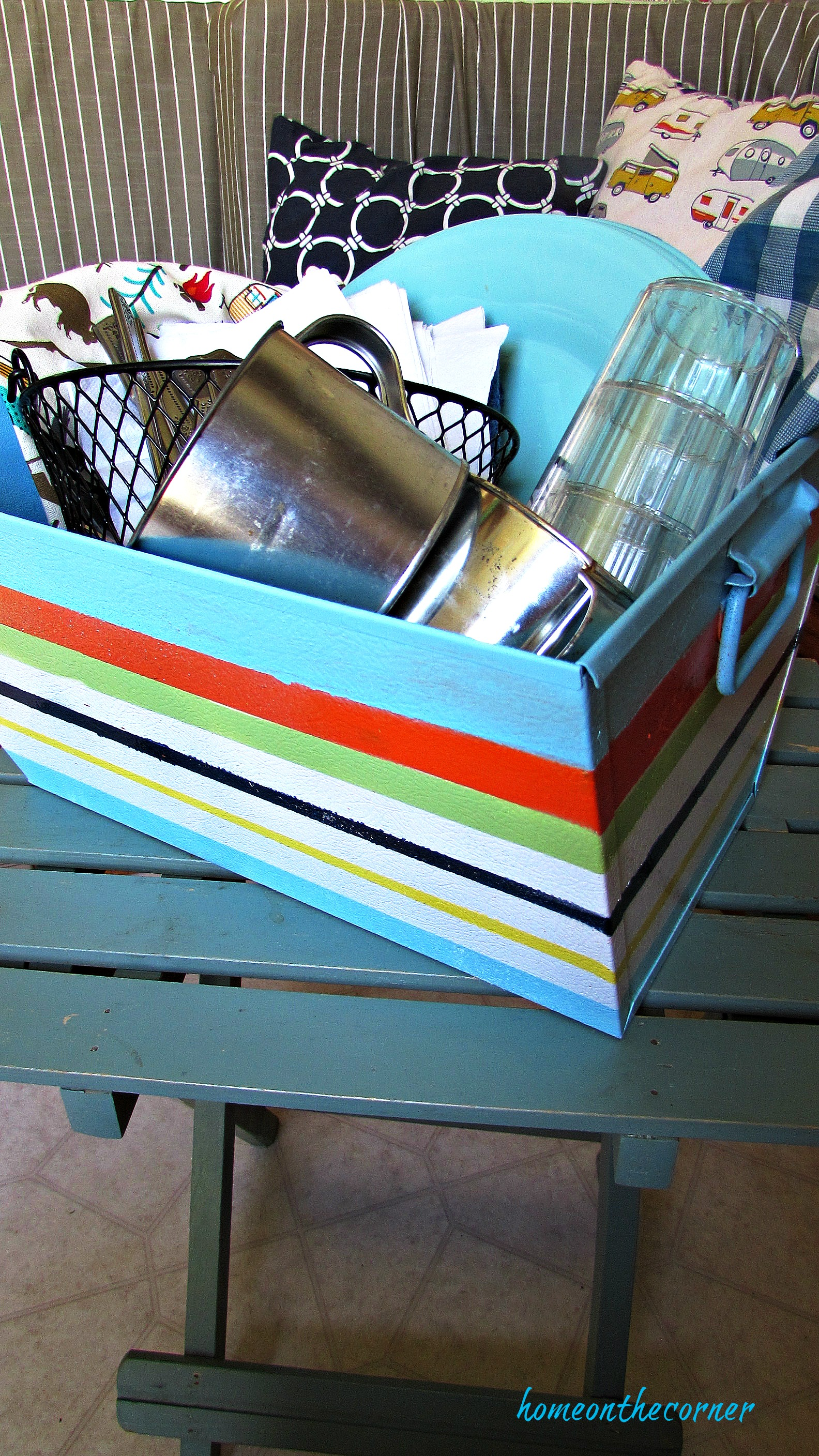metal box with painted stripes and dishes